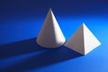 White taper and pyramid on blue geometry concept paper cone near background Royalty Free Stock Photography