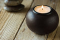 White tea light in a black wood candle holder and zen balanced stones in background,copyspace for text, harmony concept Royalty Free Stock Photo