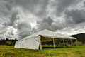 White tent under dark clouds in a field storm approaches grass Royalty Free Stock Image