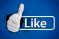 White thumb up tearing a canvas with the like from social networks on blue background Royalty Free Stock Photo