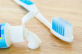 White toothpaste spill out a tube of toothpaste and toothbrush. Royalty Free Stock Photo