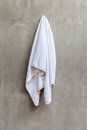 White towel is hanging on the exposed concrete wall in the bathr Royalty Free Stock Photo