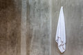 The white towel is hanging on a hanger with concrete wall in the Royalty Free Stock Photo