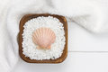 White towel with wooden bowl filled with bath salt Royalty Free Stock Photo