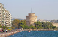 White Tower and unidentified people are walking on the embankment in Thessaloniki, Greece Royalty Free Stock Photo