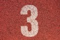 White track number on red rubber racetrack, texture of running racetracks in small outdoor stadium Royalty Free Stock Photo
