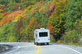 White Trailer on Highway Lined with Colorful Trees Stock Image
