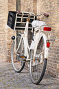 White transport bike with crate parked against brick wall, Amsterdam, Netherlands. Royalty Free Stock Photo