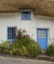 White-washed, stone cottage with thatched roof, Cadgwith, Cornwall, England Royalty Free Stock Photo