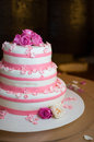 White wedding cake decorated with roses and pink sugar flowers Royalty Free Stock Image