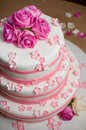 White wedding cake decorated with roses and pink sugar flowers Stock Photos
