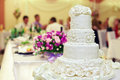 White wedding cake on interior background Stock Photos