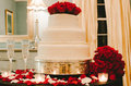 White wedding cake with red roses a three layer on top champagne glasses petals and tea lights Stock Photos