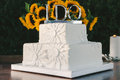 White wedding cake with silver i do topper a square flower details and a that says Stock Image