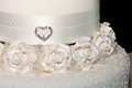 White wedding cake white ribbon heart jewellery fondant flowers royal icing Royalty Free Stock Images