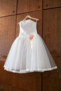White wedding dress with orange bud on hanger Stock Photo
