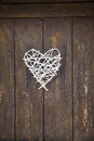 White wicker heart on old wooden door background Stock Image