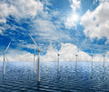 White wind turbine generating electricity on sea Royalty Free Stock Image