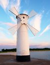 White windmill by sea on rocky coast. Seascape and landscape Royalty Free Stock Photo