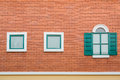 White window on the orange brick wall many shutters old Stock Image