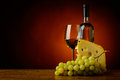 White wine cheese and grapes still life with glass bottle of Stock Photography