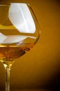 White wine into a glass with space for text warm atmosphere on golden background Royalty Free Stock Photos