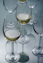 White wine glasses along with other empty glasses on a glass table Royalty Free Stock Photography