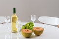 White wine melon and grapes round table with green Royalty Free Stock Images