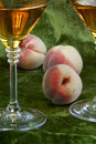 White wine and ripe peaches on green velvet Royalty Free Stock Photography