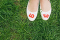 White woman shoes with red love letters green grass background top perspective before wedding engagement photo vintage color Stock Photo