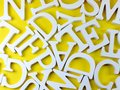 White wooden alphabet letters on yellow background Royalty Free Stock Photo
