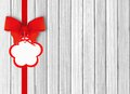 White wooden background with beautiful red bow with tag