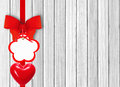 White wooden background with beautiful red bow with tag and hear