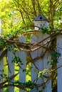 White wooden bird house on a picket fence post Royalty Free Stock Photo