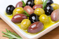 White wooden bowl with a variety of olives and rosemary in oil selective focus Royalty Free Stock Images