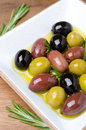 White wooden bowl with a variety of olives and rosemary in oil vertical close up Stock Photo