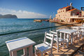 White wooden chairs and tables stand on adriatic sea coast in petrovac montenegro Royalty Free Stock Photos