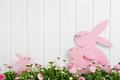 White wooden easter decoration with flowers and a pink bunny for Royalty Free Stock Photo