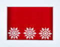 White wooden frame and snowflakes over a red background Royalty Free Stock Photo