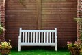 White Wooden garden bench in English garden Royalty Free Stock Photo