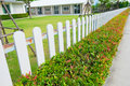 White wooden picket fence with green plant hedge. Royalty Free Stock Photo