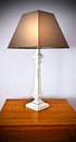 White wooden shabby chic table lamp brown shade Stock Images