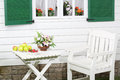 White wooden table with fruits and flowers and chair near house Royalty Free Stock Images