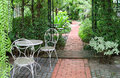 White wrought iron table and chairs in tropical garden with bricks paved walkway Royalty Free Stock Photo