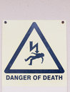 A white yellow and black close up sign on the wall saying danger