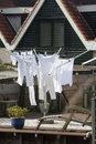 Whites only laundry wet drying in the wind in the netherlands the clothes are hanging outdoors on a rotary clothesline Stock Image