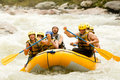 Whitewater rafting adventure group of mixed tourist men and women with guided by professional pilot on river in ecuador Royalty Free Stock Image