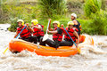 Whitewater river rafting boat adventure group of mixed tourist men and women with guided by professional pilot on in ecuador Stock Images