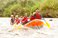Whitewater river rafting boat adventure group of mixed tourist men and women with guided by professional pilot on in ecuador Stock Image