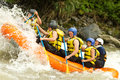 Whitewater river rafting group of mixed tourist men and women with guided by professional pilot on in ecuador Royalty Free Stock Photography